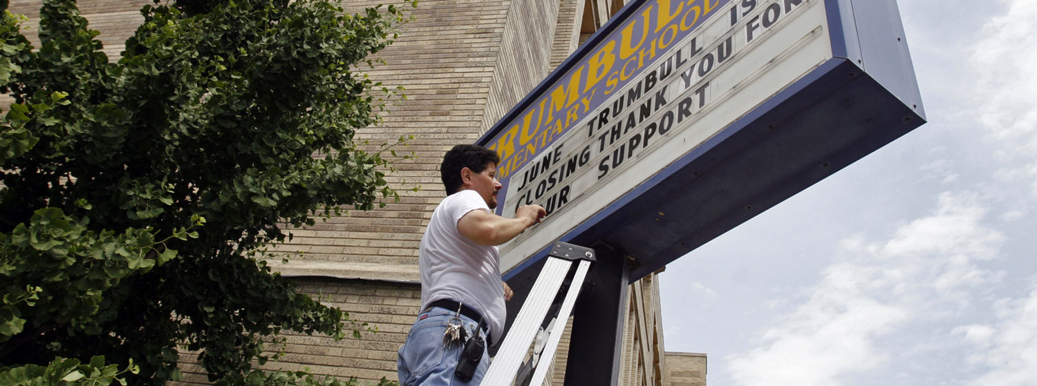 Worker changing words on school sign