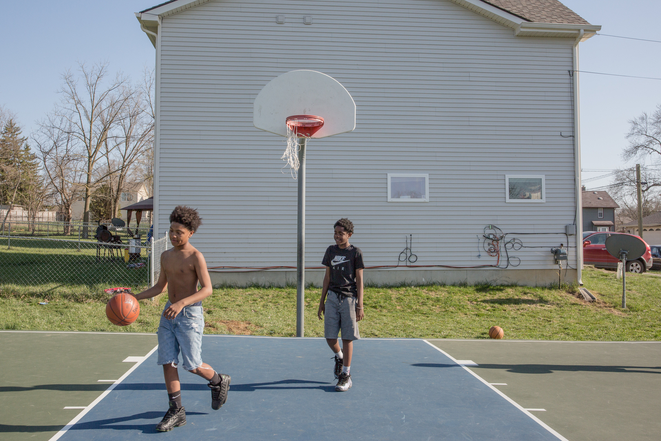 Two teenage boys play basketball outside on a community court.