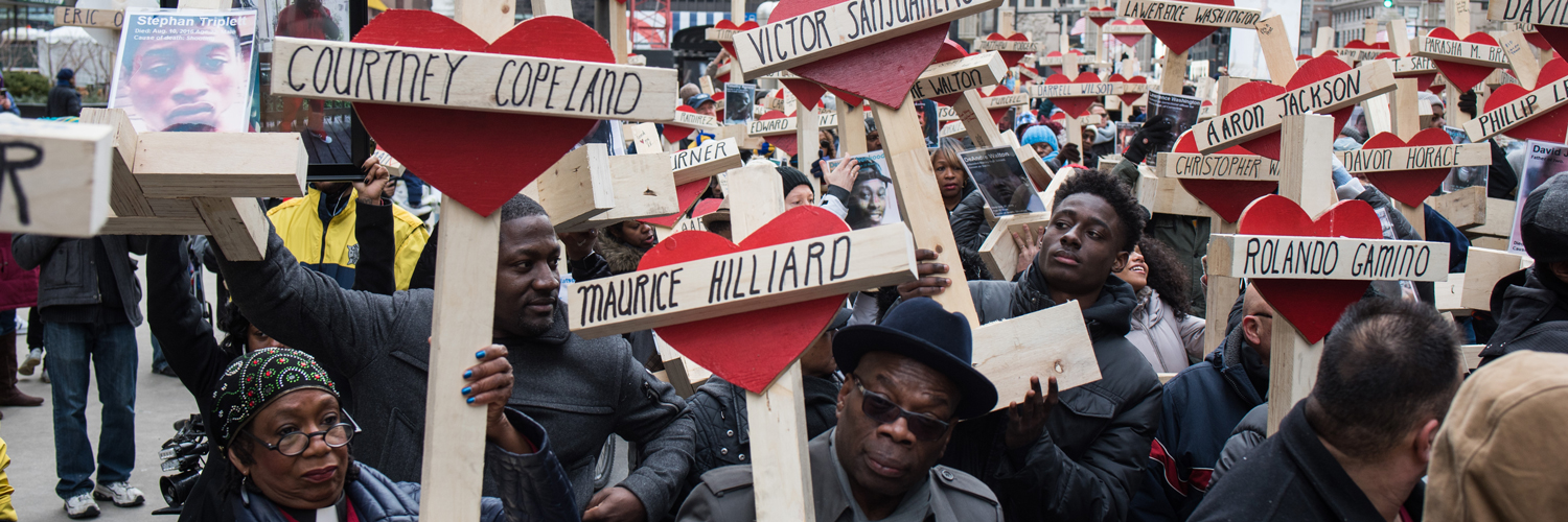 People raise over 750 wooden crosses which are dedicated to lives lost in 2016 in Chicago during a peace march on December 31, 2016.