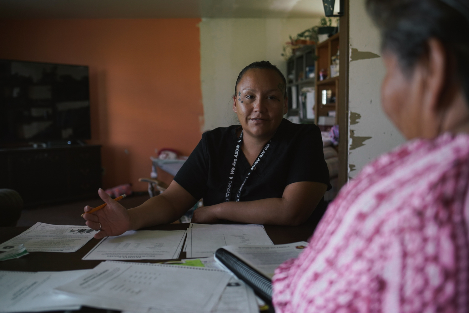 Desirae goes over budgeting worksheets with Elsie Charging Crow, a home educator with Wind River's Family Spirit home visiting program. Elsie, an elder on the Wind River Indian Reservation, teaches parents in the program about healthy child development, life skills, and Northern Arapaho traditions around parenting.