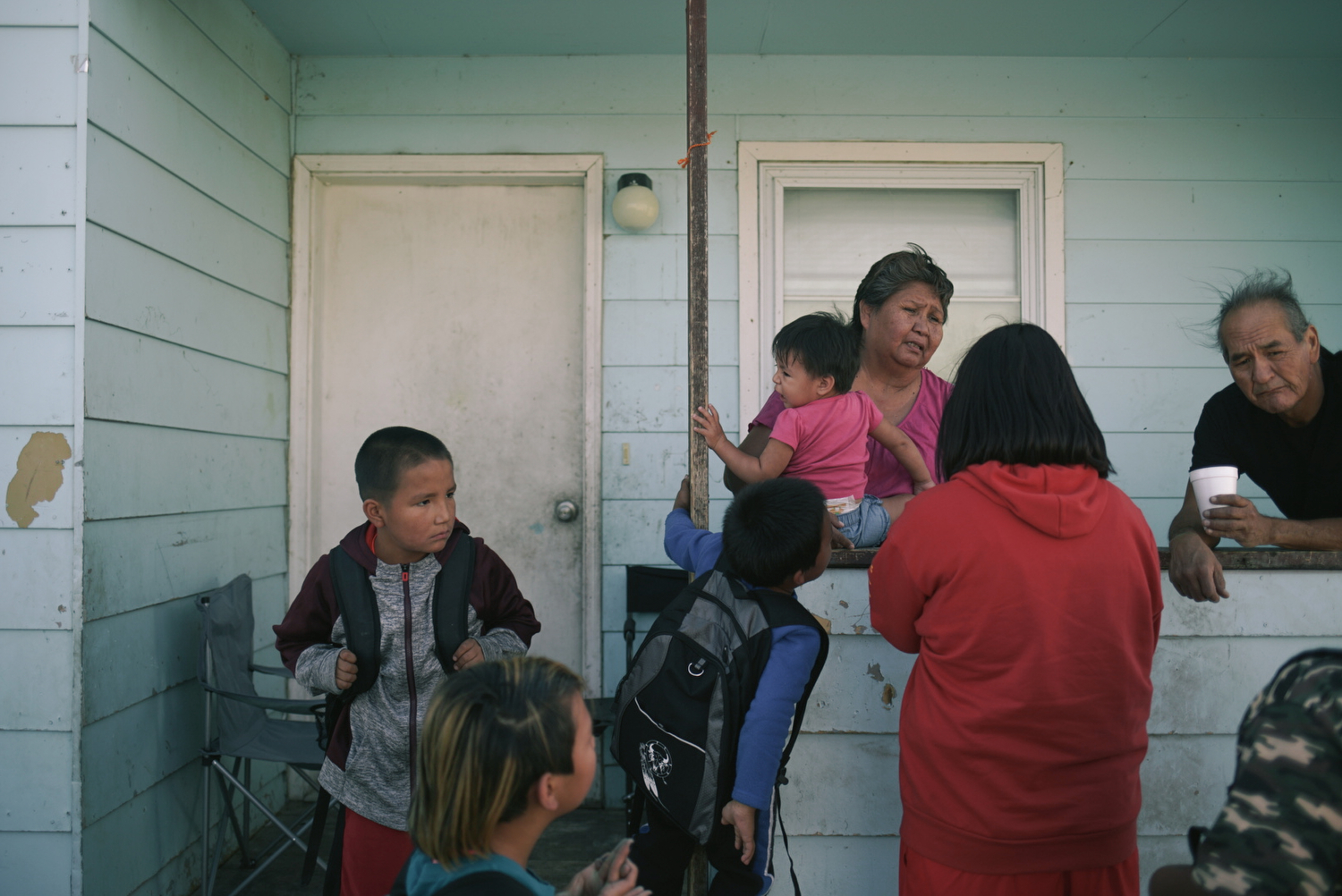 Elsie greets her grandchildren, whom she raises, as they come home from school.