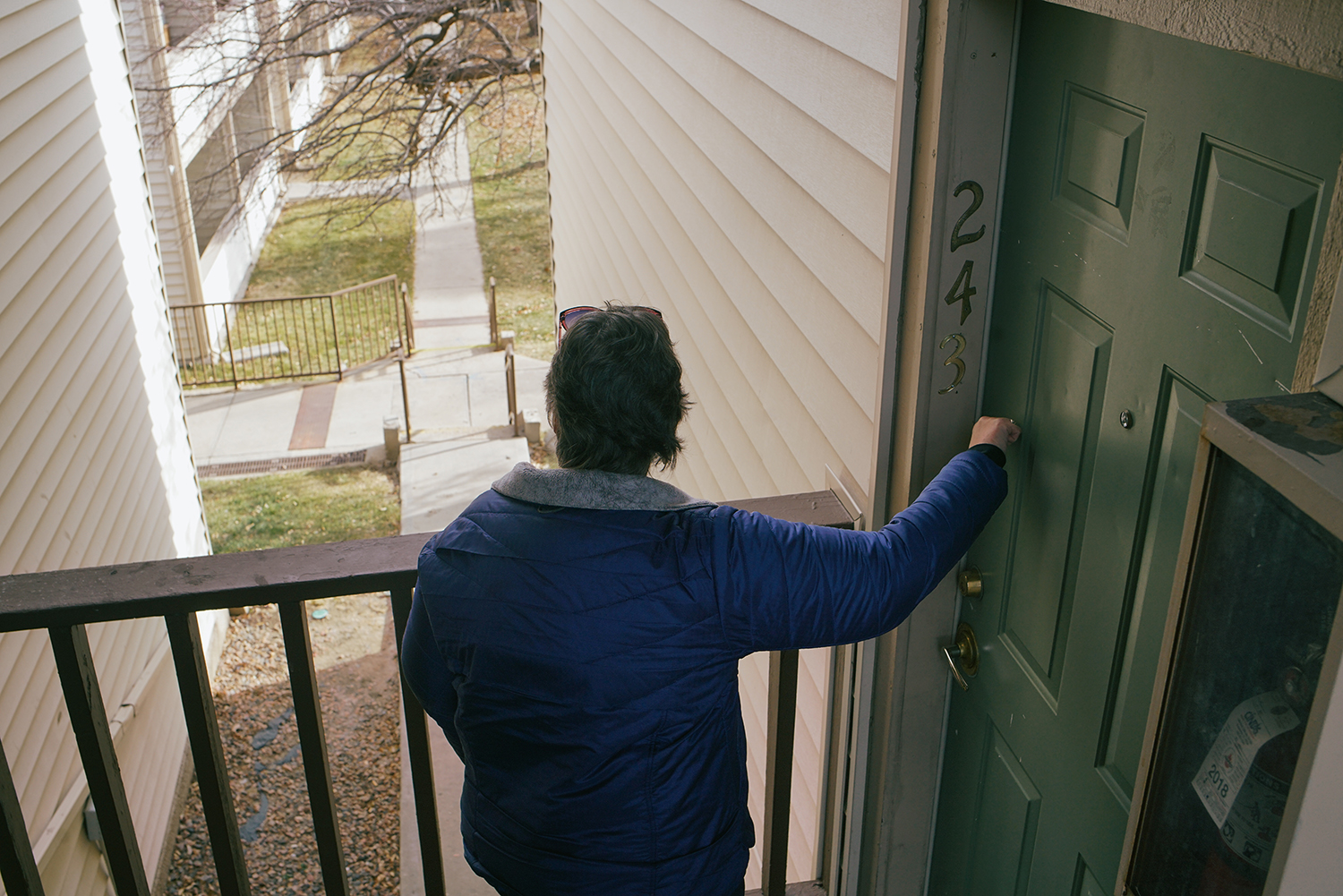 Lisa Bryant, a clinical case manager with Mental Health Center of Denver, knocks on the apartment door of a program participant who uses his social impact bond housing voucher to live in a private apartment complex.